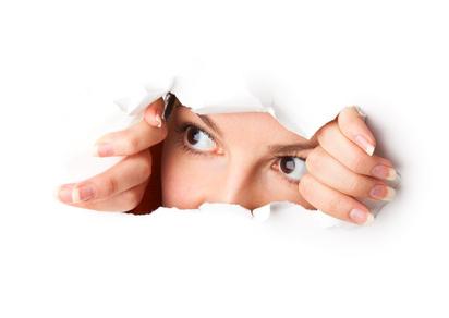 Eine Frau schaut durch ein aufgerissenes Loch von hinten auf diese Webseite