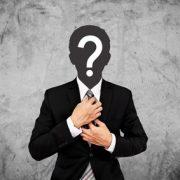 Business-Mann mit Anzug und Fragezeichen im Gesicht