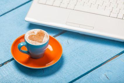 Eine Tasse mit Kaffee und einem Herz aus Schokopulver vor einem Notebook
