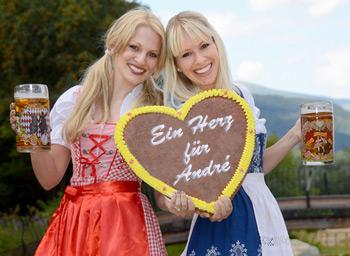Zwei blonde Mädels im Dirndl Halten gefüllte Biergläser und ein Lebkuchenherz mit der Aufschrift: Ein Herz für André